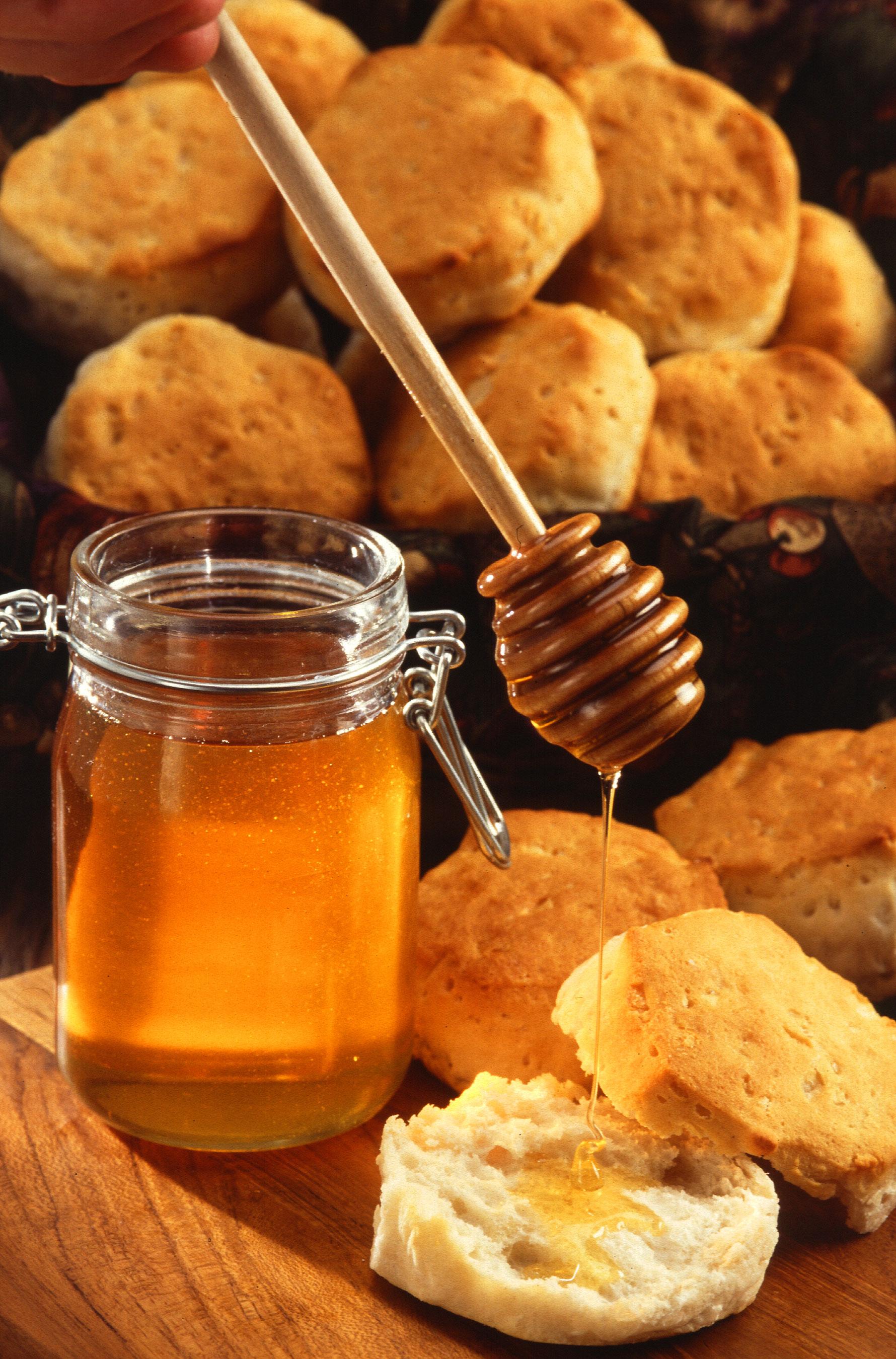 Miel en un moderno envase de cristal y un dosificador (rodillo de miel)